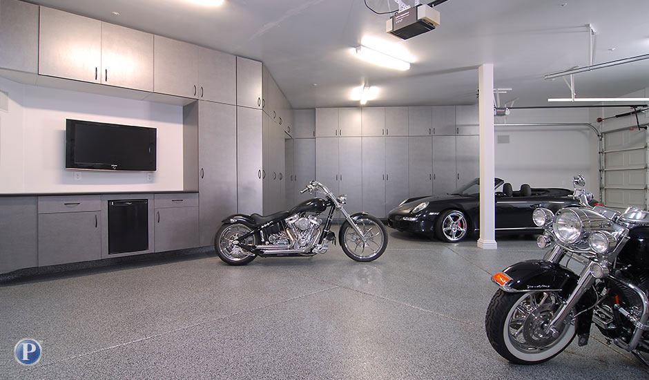 gray garage cabinets and flooring with motorcycles
